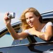 Tourist taking photographs from a car window — Stock Photo