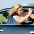 Attractive woman photographing from car window — Stock Photo