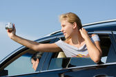 Young woman taking photos from a car — Stock Photo