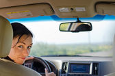 Woman driver looking into rear seat — Stock Photo