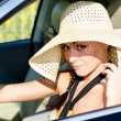 Woman driver wearing large straw sunhat — Stock Photo