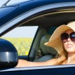 Woman driving in hat and sunglasses — Stock Photo