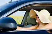 Woman in sunhat driving a car — Stock Photo