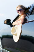 Woman with straw hat leaning from car — Stock Photo