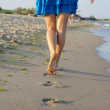 Barefoot woman walking on wet sand — Stock Photo #12226478