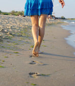 Barefoot woman walking on wet sand — Stock Photo