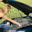 Woman checking the engine oil — Stock Photo