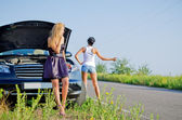 Women hitchhiking after a breakdown — Stok fotoğraf