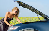Woman looking at her car engine — Stock Photo