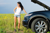 Woman in shorts with broken down car — Stock Photo