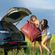 Women loading a heavy bag into car — Stock Photo
