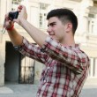 Smiling young man taking a photograph — Stock Photo