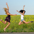Two women leaping for joy - Stock Photo
