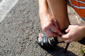Woman tightening the strap on her sandal — Stock Photo