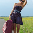 Woman walking with luggage in the country — Stock Photo