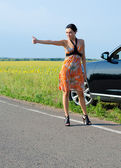 Woman hitchhiking after a breakdown — Stock Photo