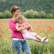 Mother and daughter in poppy field — Stock Photo #10780267