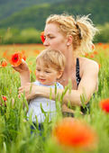 Mother and son in poppy field — Stock Photo