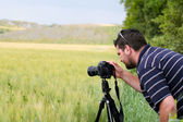 Photographer with tripod and DSLR camera — Stock Photo