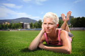 Active woman lying on green grass — Stock Photo