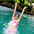 Stock Photo: Young girl jumps backward into swimming pool