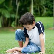 Young boy enjoying his reading book in outdoor park — Foto de Stock
