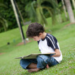 Stock Photo: Young boy enjoying his reading book in outdoor park