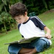 Young boy enjoying his reading book in outdoor park — Stock Photo #11969294