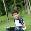 Young boy enjoying his reading book in outdoor park — Stock Photo #11969295