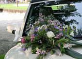 Bouquet of flowers on the hood of the car of the newlyweds — Stock Photo