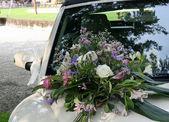 新婚の車のボンネットの上に花の花束 — ストック写真