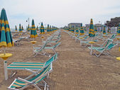 Closed Sun umbrellas and deck chairs and beds from the sea on a — Stock Photo