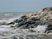 Splashing of the water of the Mediterranean Sea on the rocks on — 图库照片