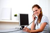 Friendly blonde secretary speaking on phone — Stock Photo