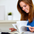 Blonde friendly young girl browsing a book — Stock Photo
