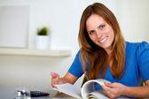 Donna bella e giovane leggendo un libro a casa — Foto Stock