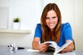 Härlig ung kvinna ler och läsa en bok — Stockfoto