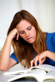 Beautiful tired blonde young girl studying — Stock Photo