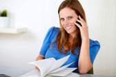 Blonde girl on cellphone while studying — Stock Photo