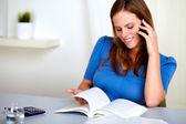 Mooi mooi meisje glimlachend en het doorbladeren van een boek — Stockfoto