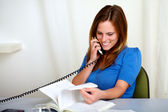 Attractive blonde young woman conversing on phone — Stock Photo