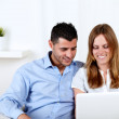 Young couple smiling and using a laptop — Stock Photo