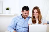 Jovem casal sorrindo e usando um laptop — Fotografia Stock