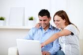 Genç çift gülümsüyor ve dizüstü bilgisayar ekranı için işaret — Stok fotoğraf