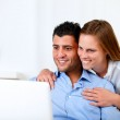 Smiling young couple using laptop — Stock Photo