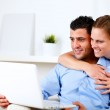 Charming couple using laptop together — Stock Photo