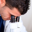 Professional medical man using a microscope — Stock Photo #11421774