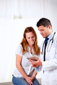 ハンサムな医者とタブレット pc を探している患者 — ストック写真