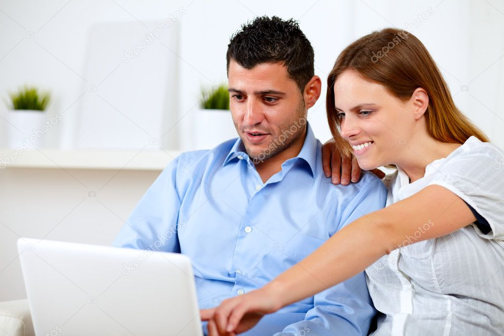 Portrait of a charming young couple sitting on sofa using laptop at home indoor  Stock Photo #11421593