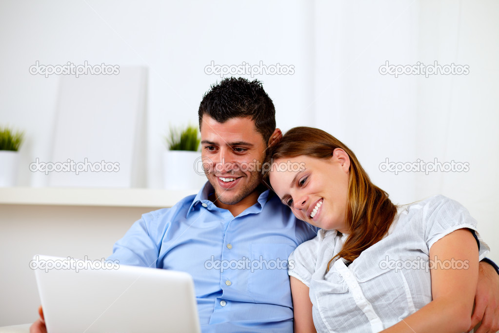 Portrait of a happy young couple sitting on sofa with a laptop at home — Stock Photo #11421597